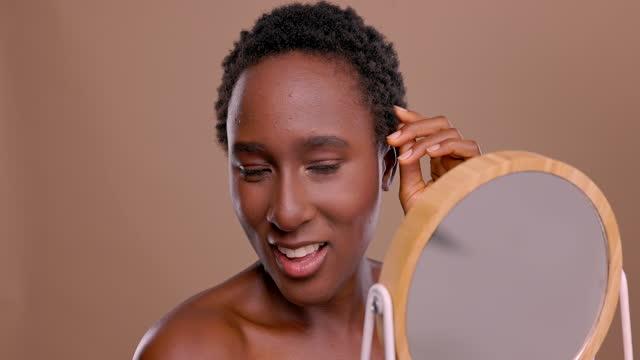 vídeos de stock e filmes b-roll de 4k video footage of a woman looking into a vanity mirror while standing against a brown background - cabelo curto comprimento de cabelo