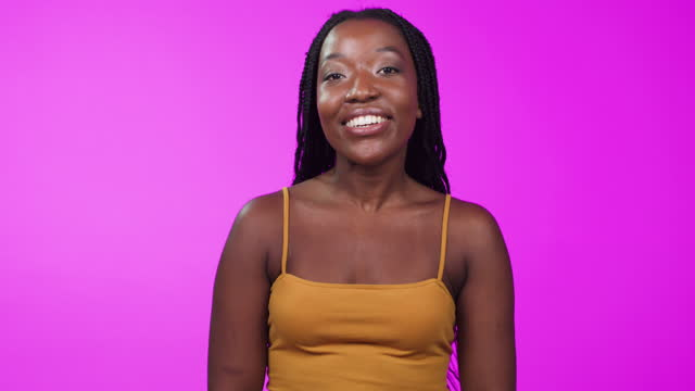 4k video footage of a woman talking at the camera while standing against a pink background - presenter stock videos & royalty-free footage