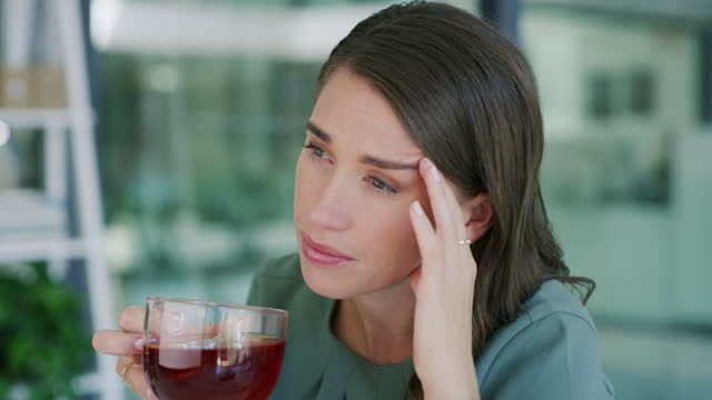 vídeos de stock e filmes b-roll de 4k video footage of a young businesswoman having a tea and feeling unwell in a modern office - excesso de trabalho