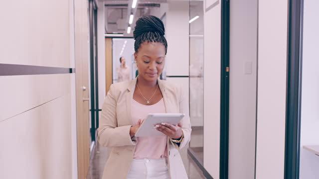 vidéos et rushes de séquences vidéo 4k d'une jeune femme d'affaires utilisant une tablette numérique tout en marchant dans un bureau moderne - directrice