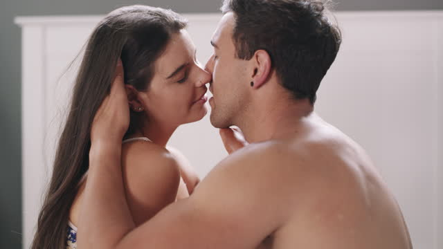 4k video footage of a young couple being intimate in bed at home - passion stock videos & royalty-free footage