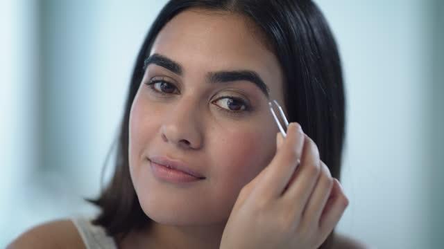 vidéos et rushes de vidéo 4k d'une jeune femme cueillant ses sourcils à la maison - seulement des jeunes femmes