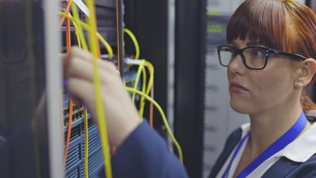 4k video footage of a young it technician standing alone in a server room and performing a maintenance check - it support stock videos & royalty-free footage