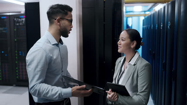4k video footage of a young man and woman shaking hands while working in a server room - colleague stock videos & royalty-free footage