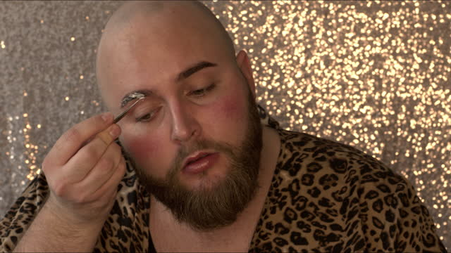 4k video footage of a young man applying makeup on his face in a studio - males stock videos & royalty-free footage