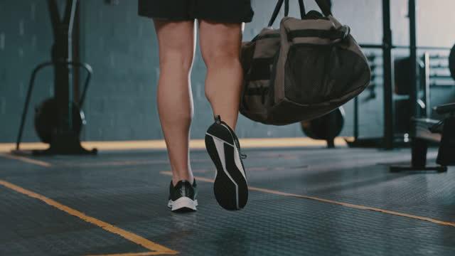 riprese video 4k di un giovane che porta una borsa sportiva mentre cammina in palestra - entrata video stock e b–roll