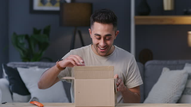 4k video footage of a young man opening a package at home - box container stock videos & royalty-free footage