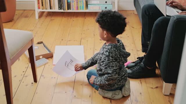 vidéos et rushes de 4k vidéo d'un jeune homme à l'aide d'un ordinateur portable et d'écouteurs sur le canapé tandis que son fils dessine à la maison - son
