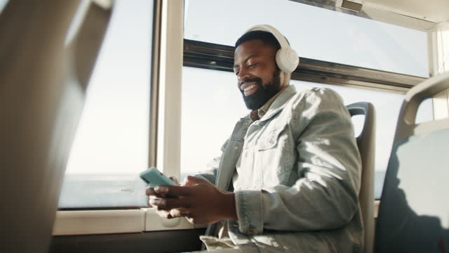 4k video footage of a young man using a smartphone and headphones while traveling on a bus - commercial land vehicle stock videos & royalty-free footage