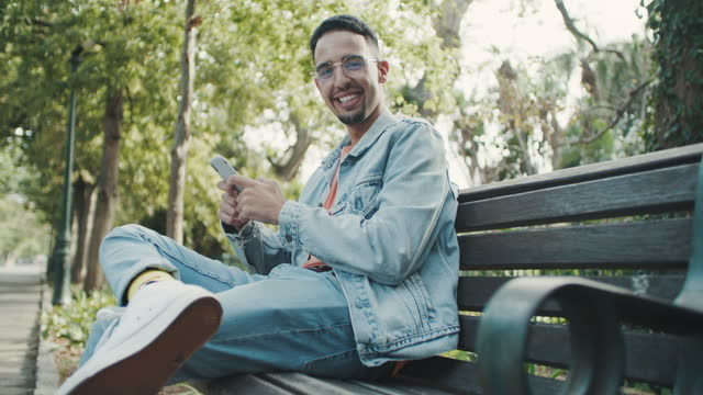 4k video footage of a young man using a smartphone while relaxing on a bench in the park - brown hair stock videos & royalty-free footage