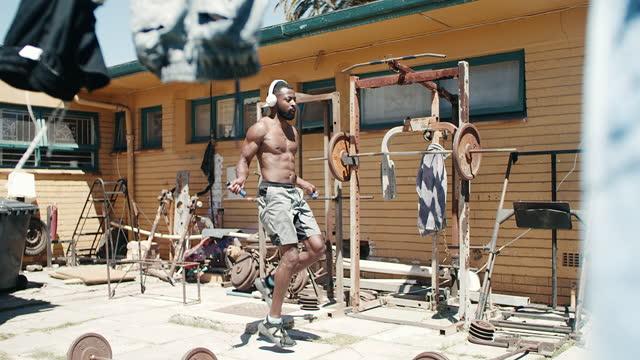 自宅の裏庭でジャンプロープで働く若い男の4kビデオ映像 - 人間の消化器官点の映像素材/bロール