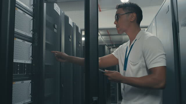 4k video footage of a young technician using a digital tablet while performing a maintenance check in a server room - digital native stock videos & royalty-free footage