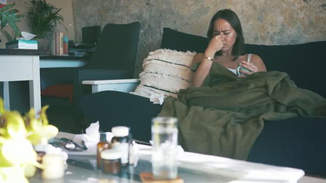 vídeos y material grabado en eventos de stock de imágenes de vídeo de 4k de una joven soplando su nariz mientras estaba sentada en el sofá en casa - manta ropa de cama