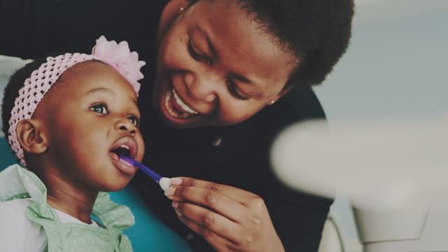 4k video footage of a young woman brushing her adorable daughter's teeth in a dentist's chair - brushing stock videos & royalty-free footage
