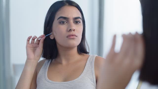 4k video footage of a young woman cleaning her ear at home - endast unga kvinnor bildbanksvideor och videomaterial från bakom kulisserna