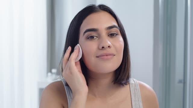 vidéos et rushes de vidéo 4k d'une jeune femme se nettoyant le visage dans la salle de bain à la maison - seulement des jeunes femmes