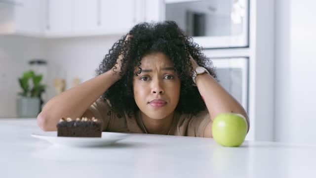 stockvideo's en b-roll-footage met 4k videobeelden van een jonge vrouw die beslist of ze thuis een appel of een chocolade brownie wil hebben - keus