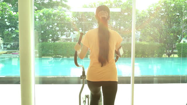 stockvideo's en b-roll-footage met 4k video footage of a young woman doing exercise at gym room - jogster