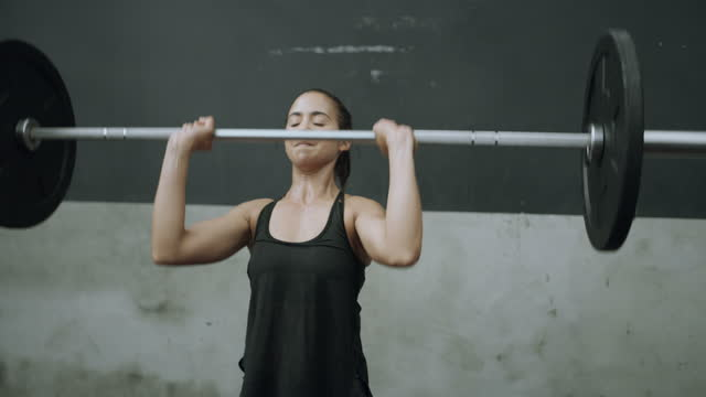 4k video footage of a young woman doing overhead presses with a barbell in a gym - picking up stock videos & royalty-free footage