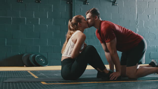 4k video footage of a young woman doing sit ups with the help of her boyfriend in a gym - sportsperson stock videos & royalty-free footage