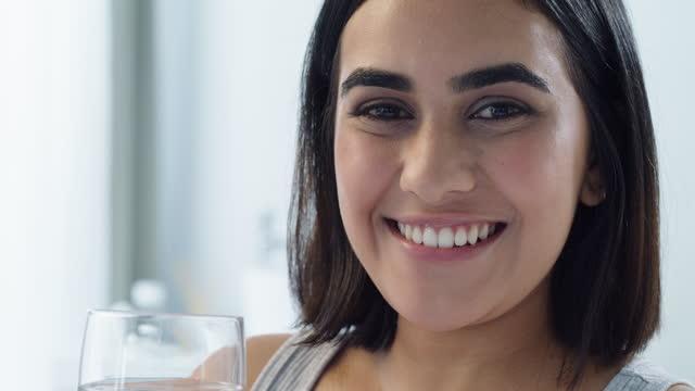 vidéos et rushes de vidéo 4k d'une jeune femme buvant de l'eau dans la salle de bain à la maison - seulement des jeunes femmes