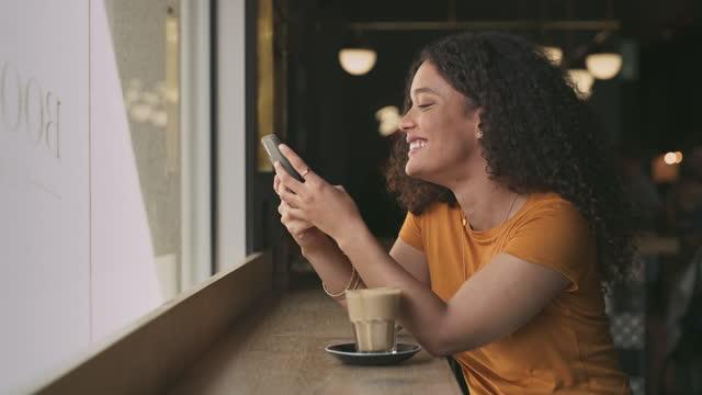 4k videofilmer av en ung kvinna som njuter av en kopp kaffe på ett kafé medan hon smsar med sin smartphone - kaffe dryck bildbanksvideor och videomaterial från bakom kulisserna