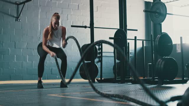 vídeos de stock e filmes b-roll de 4k video footage of a young woman exercising with battle ropes in a gym - corda