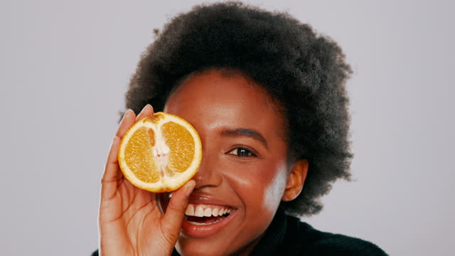 4k video footage of a young woman holding up a halved orange while posing against a grey background - glowing stock videos & royalty-free footage