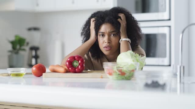 vidéos et rushes de images vidéo 4k d'une jeune femme regardant frustré tout en faisant un repas sain à la maison - adulte