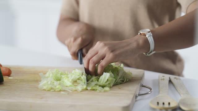 vídeos y material grabado en eventos de stock de imágenes de video de 4k de una joven haciendo una comida saludable en casa - lechuga