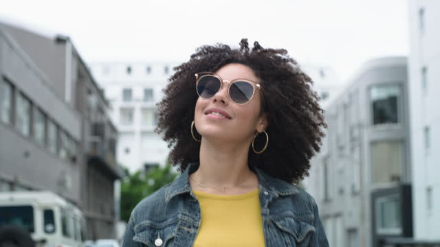 4k video footage of a young woman putting on her sunglasses while walking through the city - sunglasses stock videos & royalty-free footage