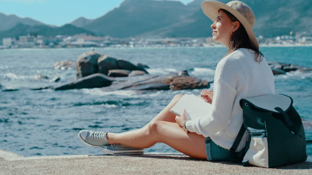 4k video footage of a young woman relaxing next to the ocean while writing notes on a notepad before admiring the view - diary stock videos & royalty-free footage