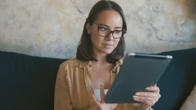 vídeos de stock, filmes e b-roll de vídeo 4k de uma jovem comprando online com seu tablet em casa - escolher