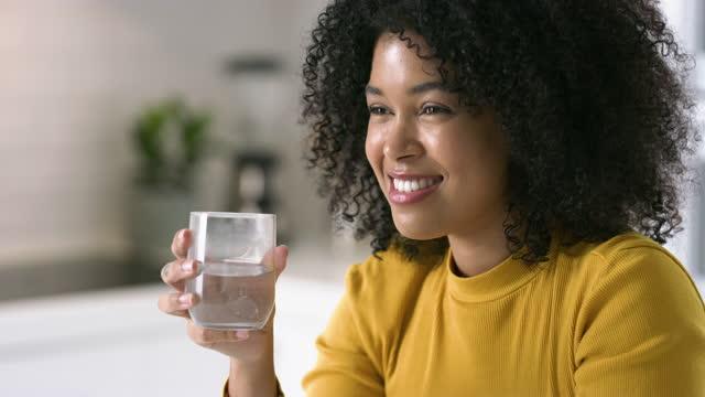 自宅の台所でコップ一杯の水でピルを飲む若い女性の4kビデオ映像 - ビタミン類点の映像素材/bロール