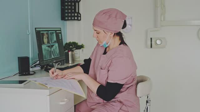 stockvideo's en b-roll-footage met 4k videobeelden van een jonge vrouw die een computer gebruikt terwijl het werken in het bureau van een tandarts - buiten de vs