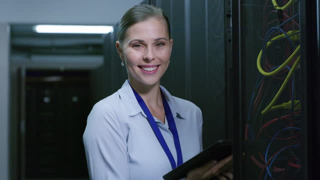 4k video footage of a young woman using a digital tablet while working in a server room - network server stock videos & royalty-free footage