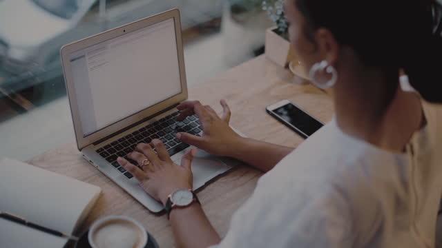 vidéos et rushes de images vidéo 4k d'une jeune femme travaillant sur un ordinateur portatif dans un café - filmer