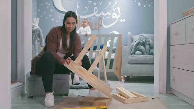 4k video footage of a young woman working on a wooden project in her baby's nursery at home - sovrum bildbanksvideor och videomaterial från bakom kulisserna