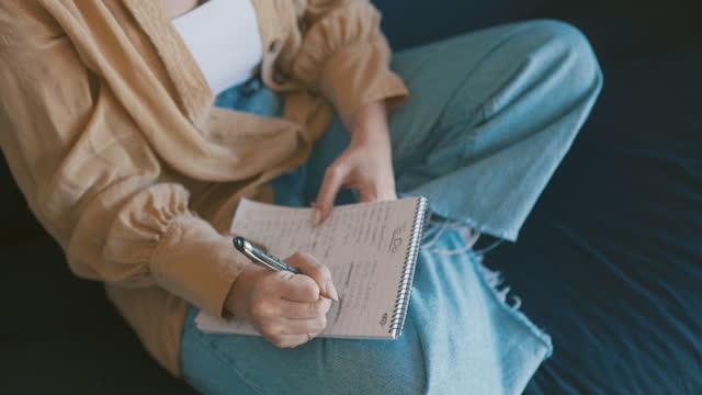 stockvideo's en b-roll-footage met 4k videobeelden van een jonge vrouw die in haar boek op de bank thuis schrijft - in kleermakerszit