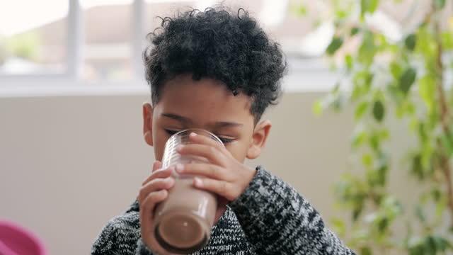 vídeos de stock, filmes e b-roll de vídeo 4k de um menino adorável tendo um milkshake de chocolate em casa - copo