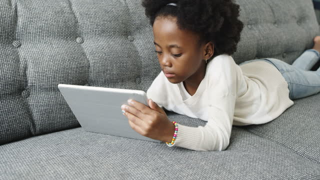 4k video footage of an adorable little girl using a digital tablet on the sofa at home - e reader stock videos & royalty-free footage