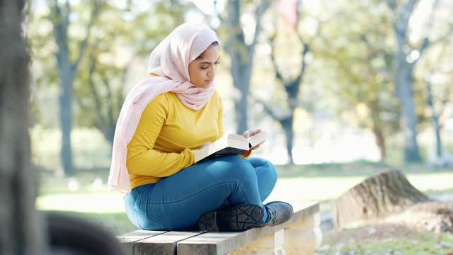 vidéos et rushes de vidéo 4k d'une jeune femme musulmane séduisante assise seule sur un banc de parc et lisant un livre - vêtement religieux