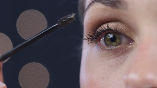 4k video footage of an attractive young woman applying mascara against a studio background - eyelash stock videos & royalty-free footage
