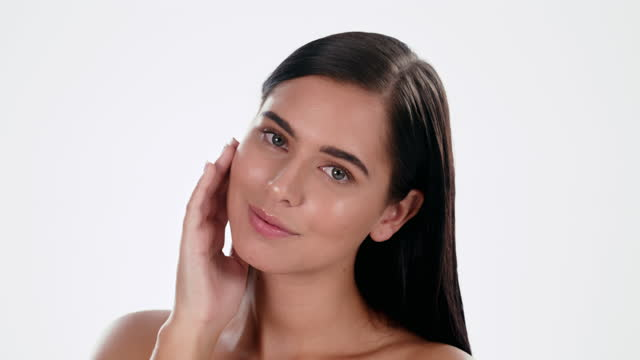 4k video footage of an attractive young woman feeling her skin against a studio background - beautiful woman stock videos & royalty-free footage