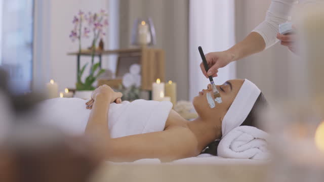 4k video footage of an attractive young woman getting a facial at a beauty spa - brown hair stock videos & royalty-free footage