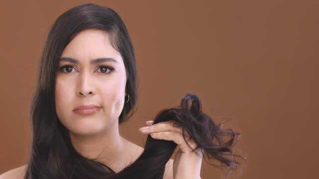 vídeos de stock, filmes e b-roll de vídeo 4k de uma jovem atraente olhando para seu cabelo e sentindo-se infeliz contra um fundo de estúdio marrom - brown hair