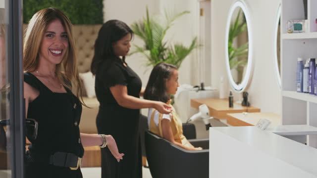 riprese video 4k di una giovane donna attraente che apre la porta del suo parrucchiere e accoglie un cliente in - entrata video stock e b–roll