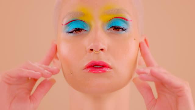 4k videoaufnahmen einer attraktiven jungen frau, die im studio vor einem cremefarbenen hintergrund posiert - halbbekleidet stock-videos und b-roll-filmmaterial