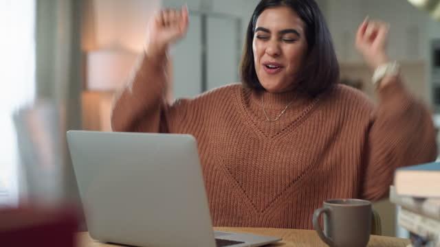 4k videoaufnahmen einer attraktiven jungen frau, die allein zu hause sitzt und eine leistung feiert, während sie ihren laptop benutzt - schulische prüfung stock-videos und b-roll-filmmaterial