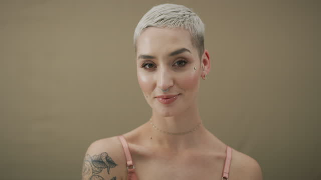 茶色のスタジオの背景に合ってポーズをとっているピアスを持つ魅力的な若い女性の4kビデオ映像 - ピアスをあけた点の映像素材/bロール
